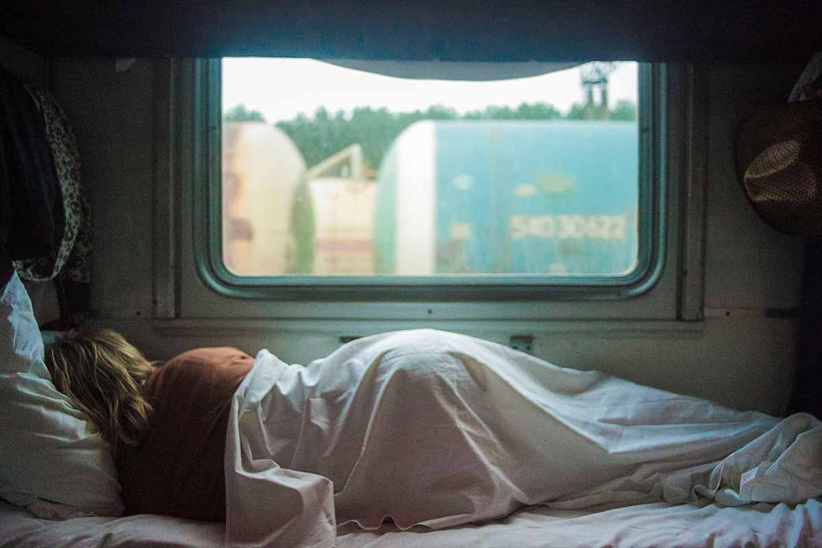 depicting sick enough; image of the back of figure laying in bed, with sheets pulled over, staring out a window