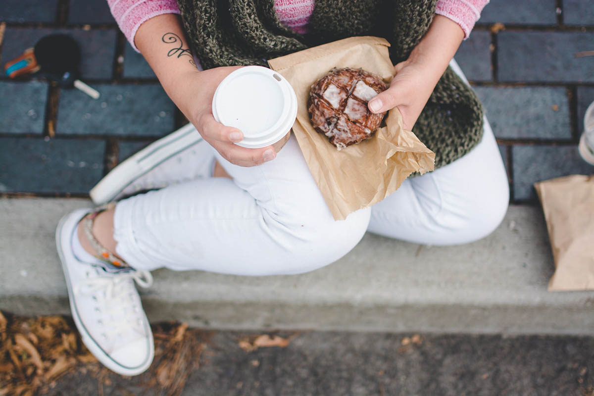 dietitian - image of person from above the knees down, sitting on a step, with a cookie and coffee
