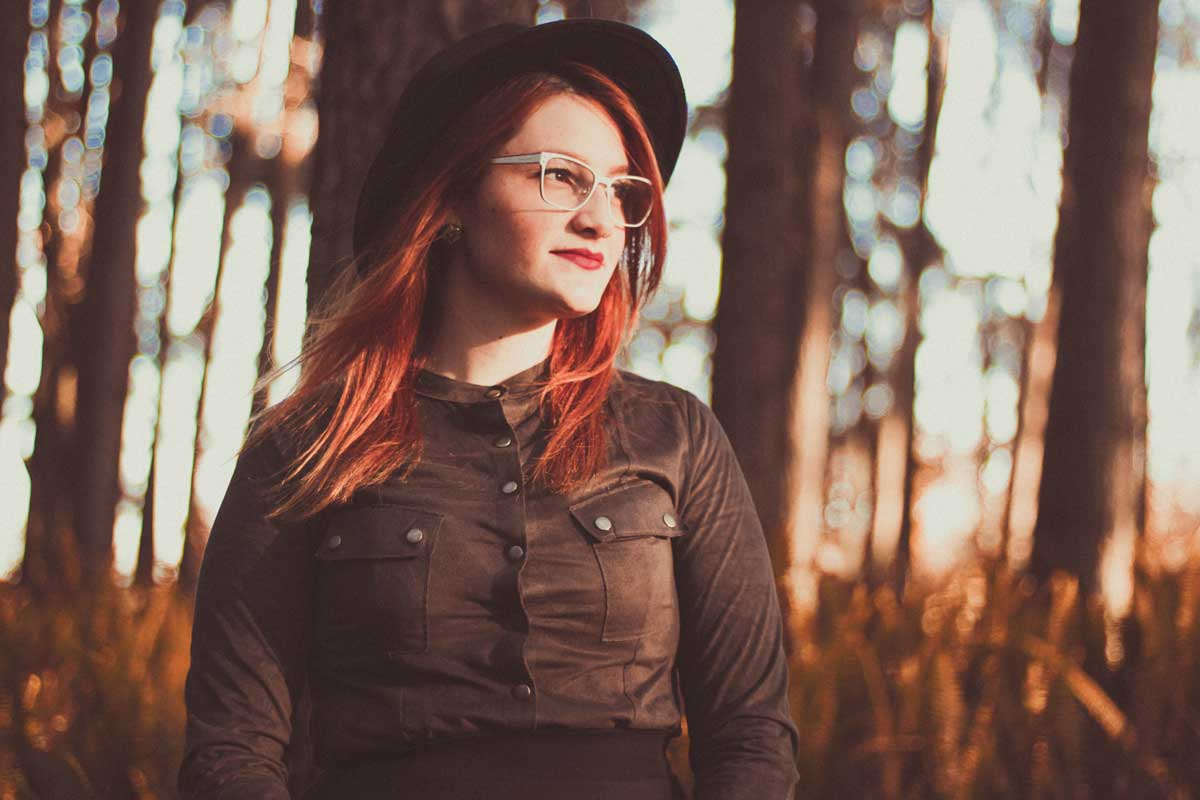 ED recovery - image of female from waist up, looking to the side with a slight smile, she is wearing black clothing, a black hat, and glasses. The background is blurred trees and sunlight shines on her face