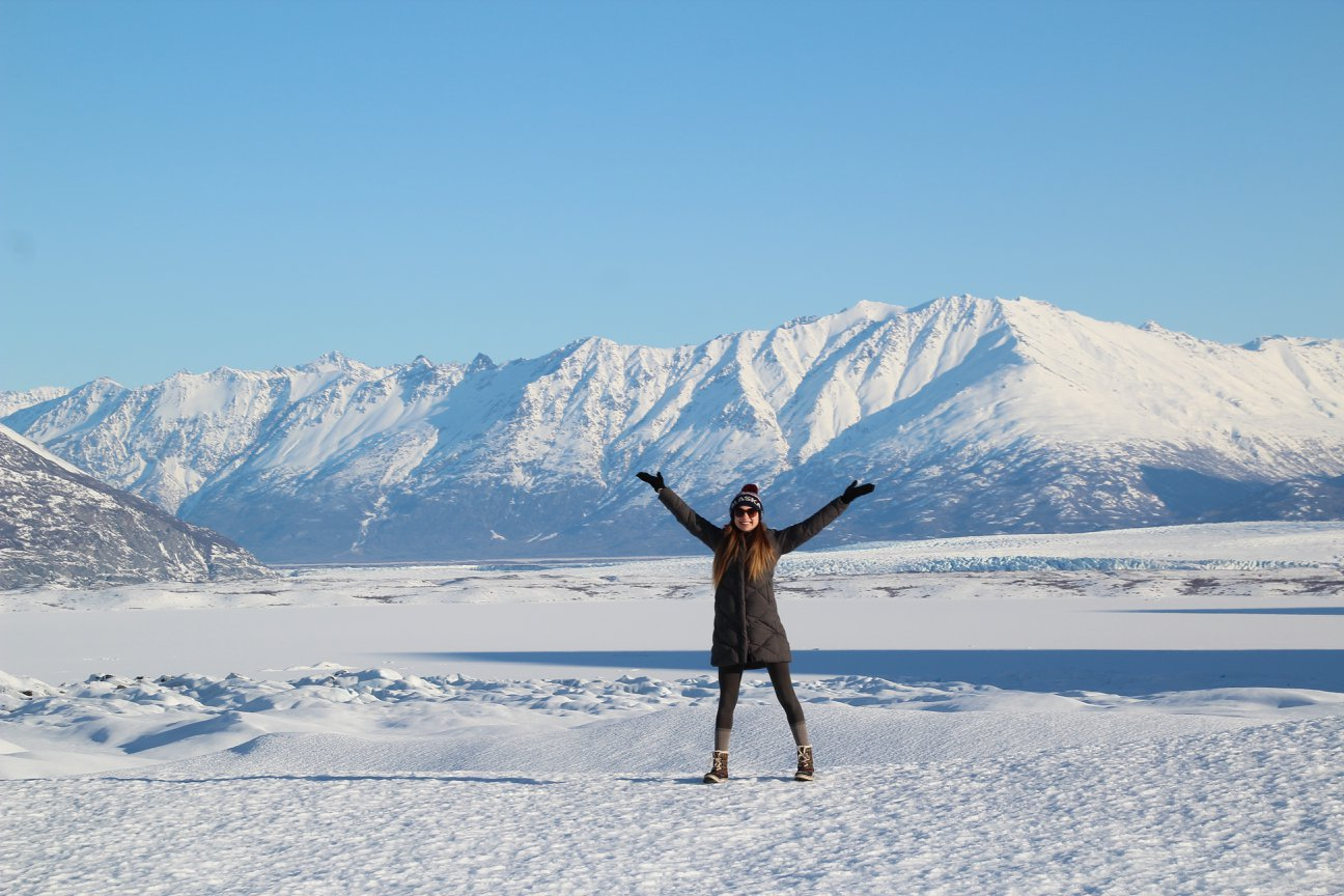 food freedom - image of figure standing in snow, in Alaska, with snow covered mountains behind, standing with feet stretched wide and arms stretched out over their head