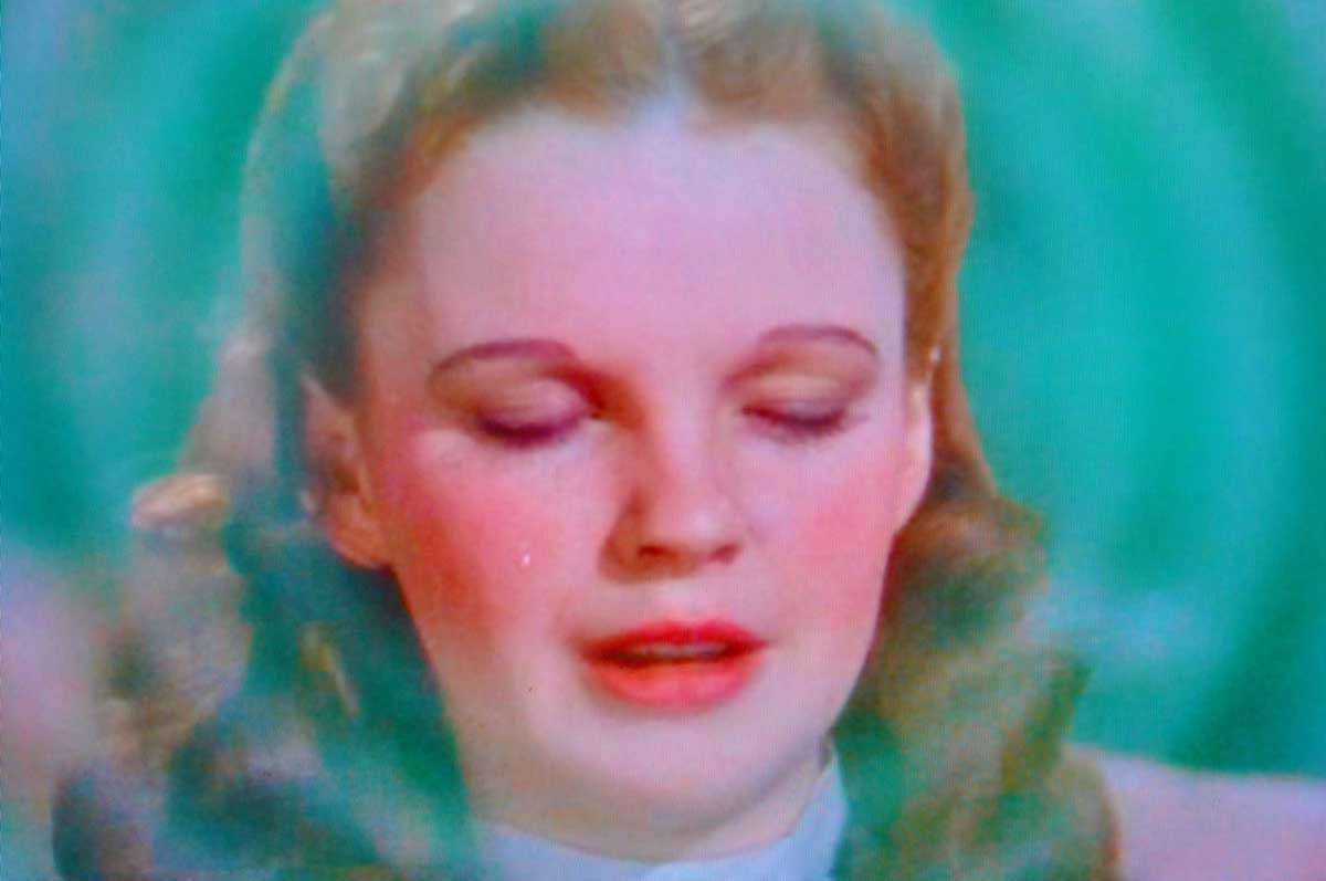 """Wizard of Oz - image of Dorothy with her eyes closed saying """"there's no place like home"""""""