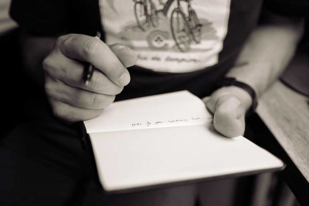 beliefs - image of hand holding a pen and a notebook