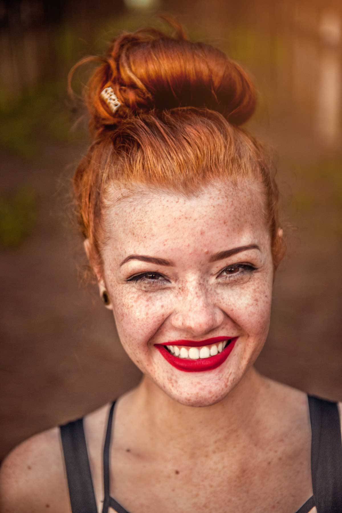 controlling food - image of woman from shoulders up, smiling directly into the camera; she has red hair piled into a bun on top of her face and her skin is covered in freckles