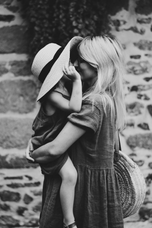 image depicting love and hopes; of a woman wearing a large hat holding a young girl, their noses are touching and you can see a smile on the woman's face