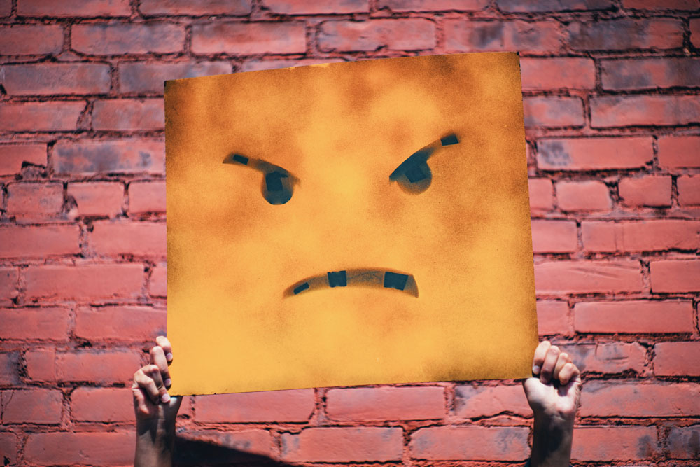 an image of hands holding up dark orange rectangular sign of an angry face depicting anger when a doctor tells you to watch your weight