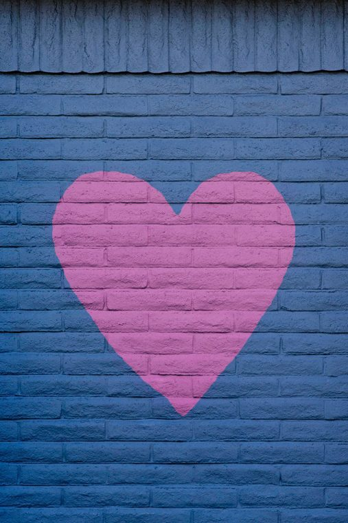 image of a blue brick wall with a pink heart painted on it to go with article about recovery from an eating disorder