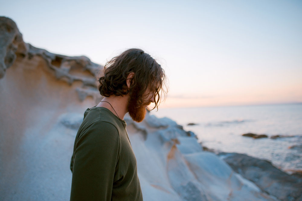 Profile of bearded man gazing down depicting feeling shame, with blurred ocean in the background