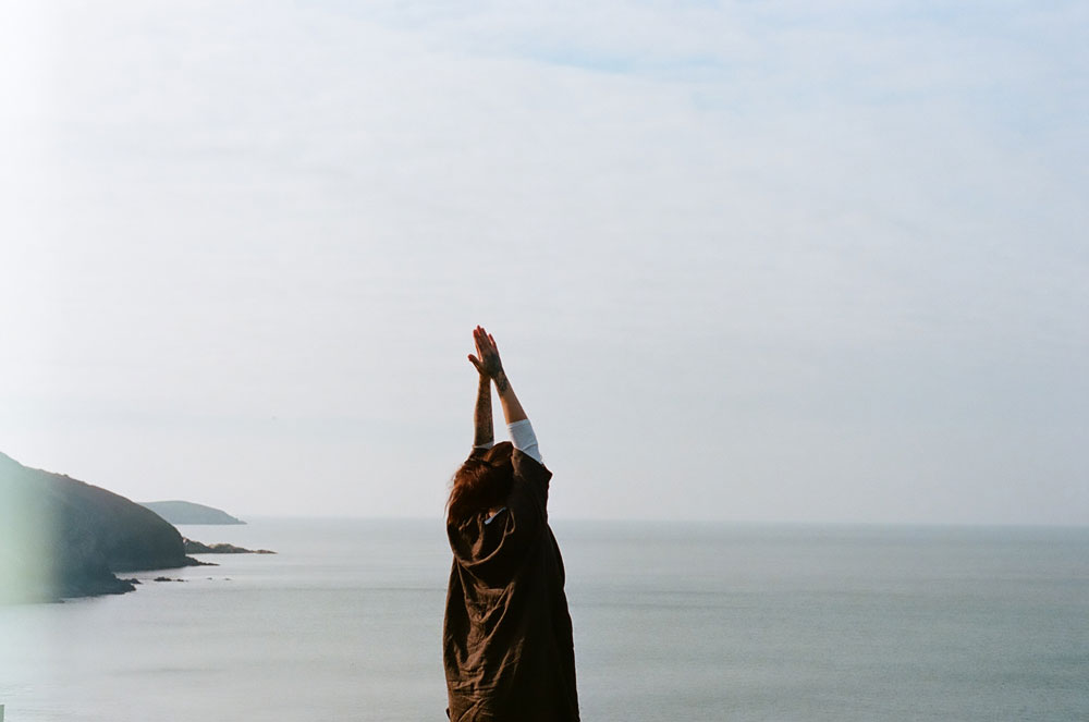 she let herself go - image of back of a figure standing in front of the ocean, with hands pressed together above the figure's head
