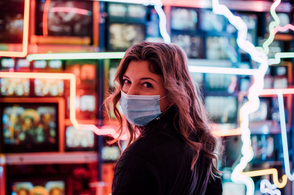 depicting staying in recovery during difficult times; image of female at a store, wearing a face mask