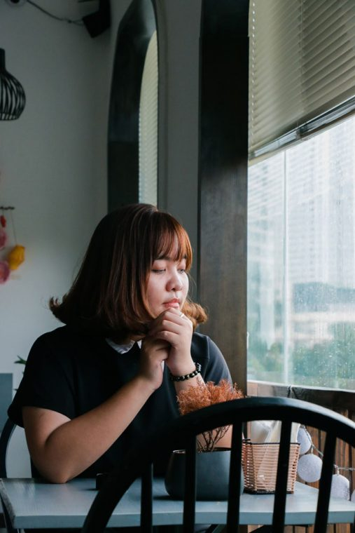 obsessing about food - image of female sitting at table staring down with serious expression on face
