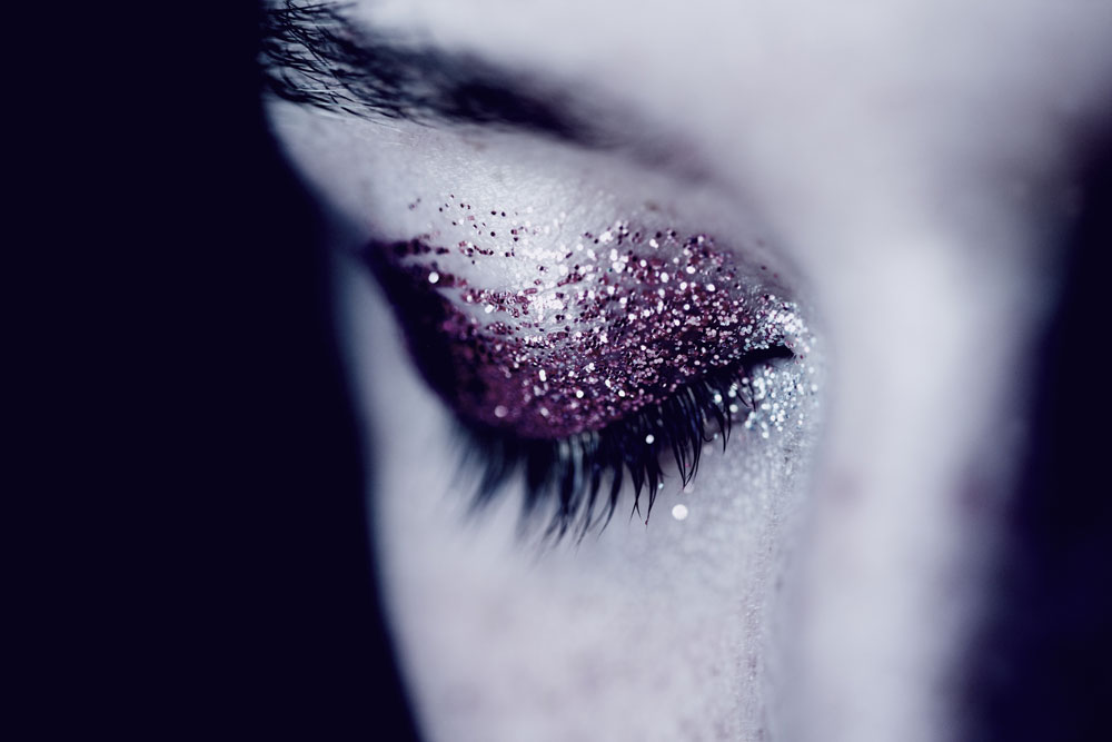 the tears - close up image of an eye that is closed, there is purple glitter eyeshadow on the eye lid and the rest of the image is black and white