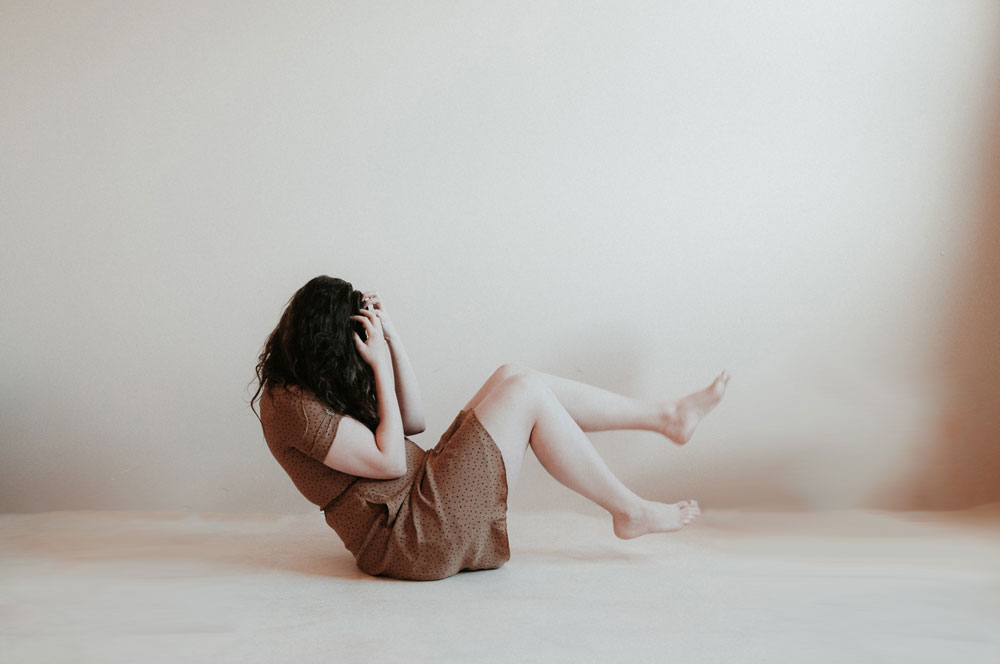 thinking about food - image of a figure sitting on the floor with hands covering their face, legs bent, and feet off the floor, background is a blank wall; image is in all grays, cream, and brown