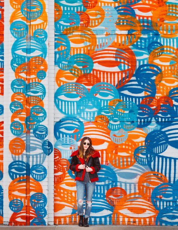 speaking up - image of a female  in dark sun glasses, wearing torn jeans and a black and red coat, standing in front of a wall covered in orange, blue, and red abstract circular designs