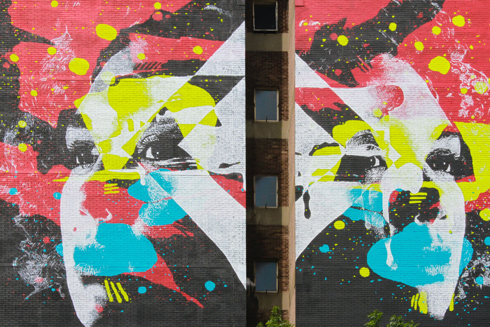 what I eat in a day post - image of a wall with abstract faces in graffiti in black, white, yellow, teal, and reds