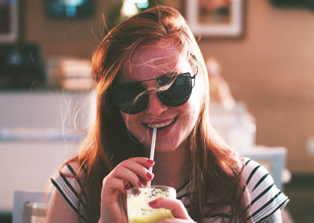 diet culture - image of female wearing sunglasses drinking from a straw with a smile