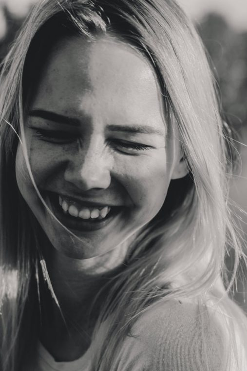 recovery from an eating disorder - close up image of female smiling with her eyes closed