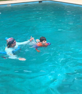 facing fear - image of same boy in the water with a huge smile on his face, his father next to him