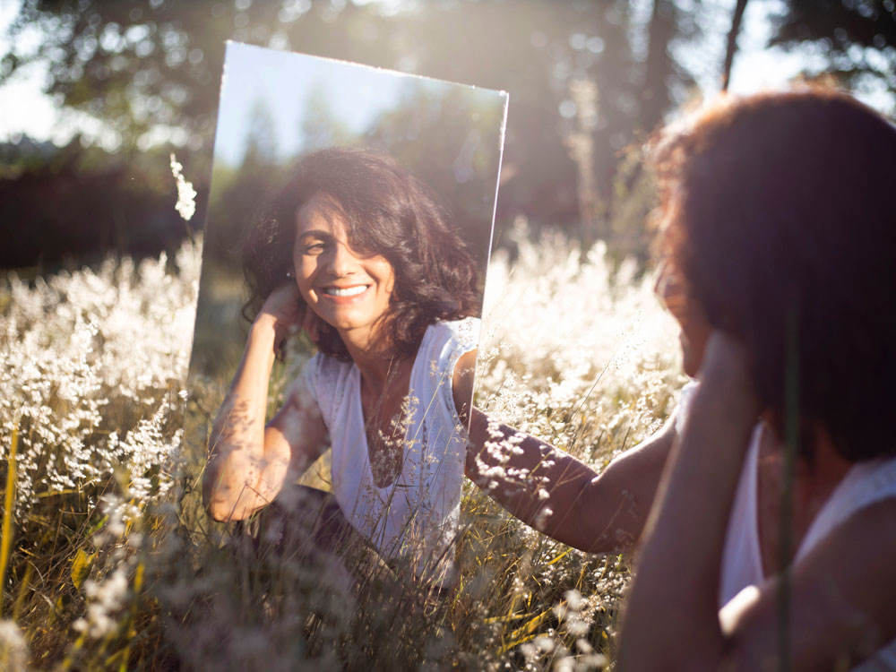comparison - image of woman in field staring at reflection of herself