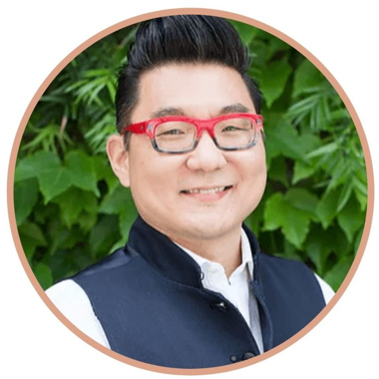 image of Dr. Norman Kim (guest on In This Body)  smiling and wearing red glasses