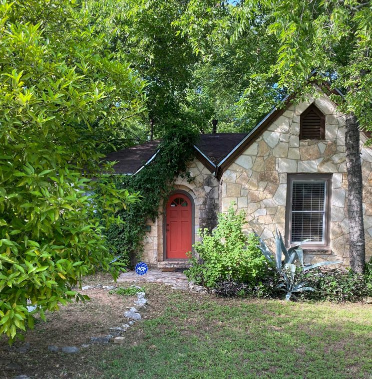 image of beloved stone cottage where Jessica Flint moved, it has a red door and lush greenery all around it