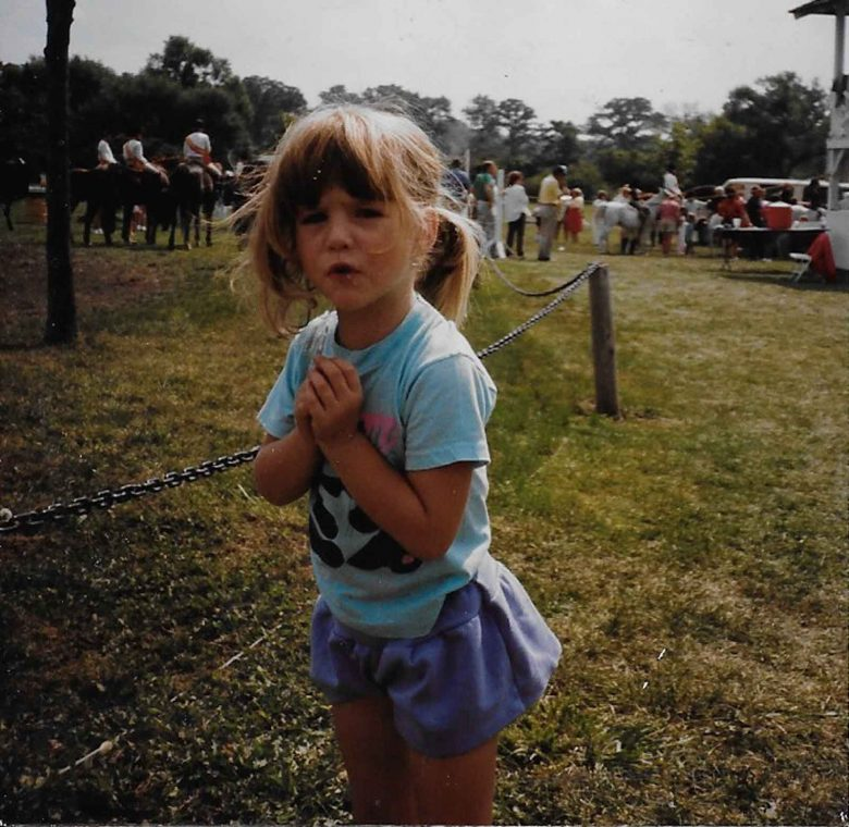 Image of a young Jessica Flint with pig tails, wearing a t-shirt and shirt, and a serious expression on her face, standing outside with horses behind her
