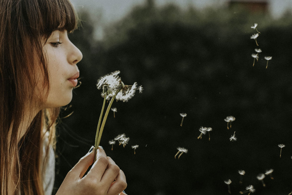 letting go eating disorder - closeup of woman's profile as she is blowing on a dandelion, seeds are floating in the air