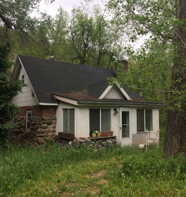 Image of white cottage tucked into the rocky mountains where I started my new journey