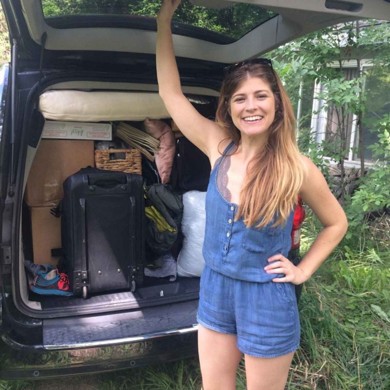 """image of Jessica Flint standing in front of her car, with hatch back open, car is filled with suitcases and belongings, she is smiling at the camera as if saying """"I'm ready to start my journey"""""""