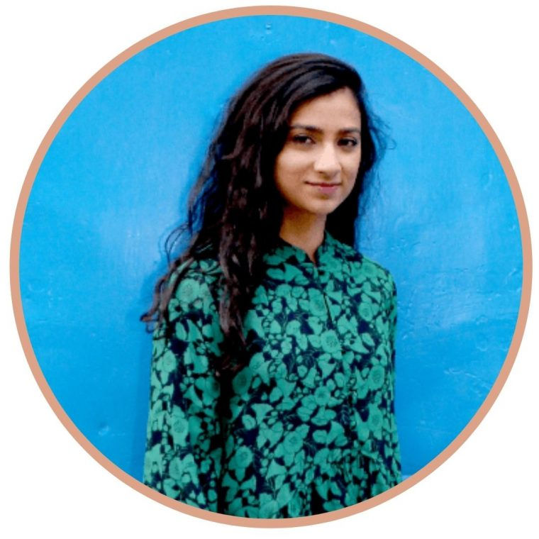 image of NAadia Craddock (guest on In This Body) from waist up, wearing a teal floral shirt, long hair, smiling slightly at camera