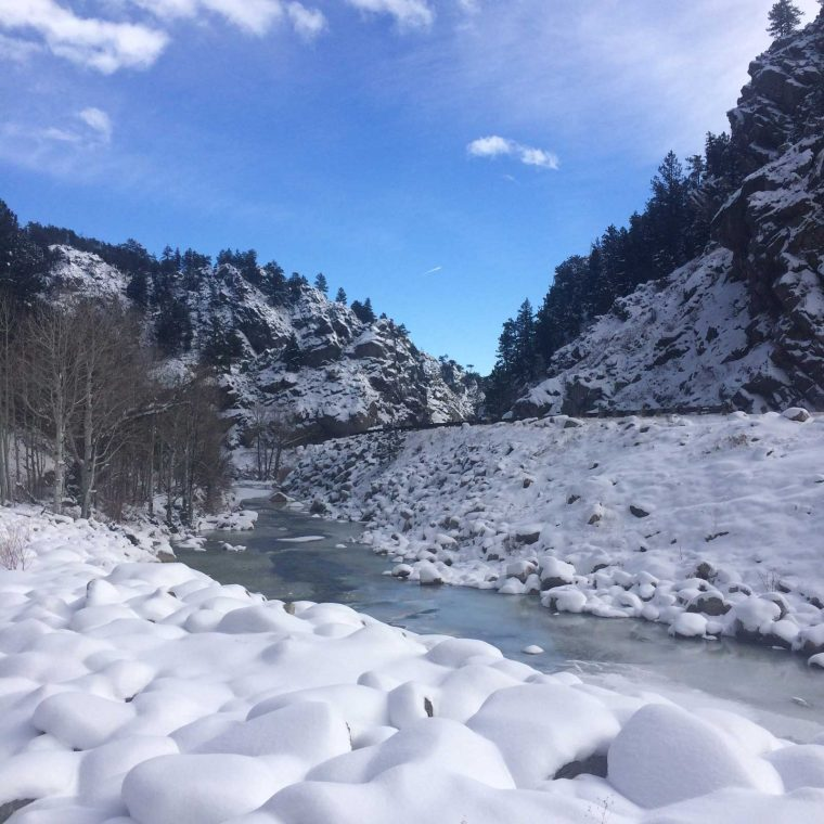 image of the river with snow covering the banks and mountains by it